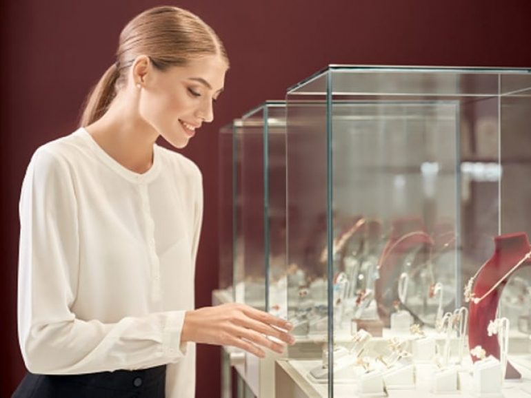 Beautiful lady with blond hair and tied knot in white silk blouse smiling and looking at showcase with luxury jewelry in store. Female assistant controling the appropriate look of precious metal.