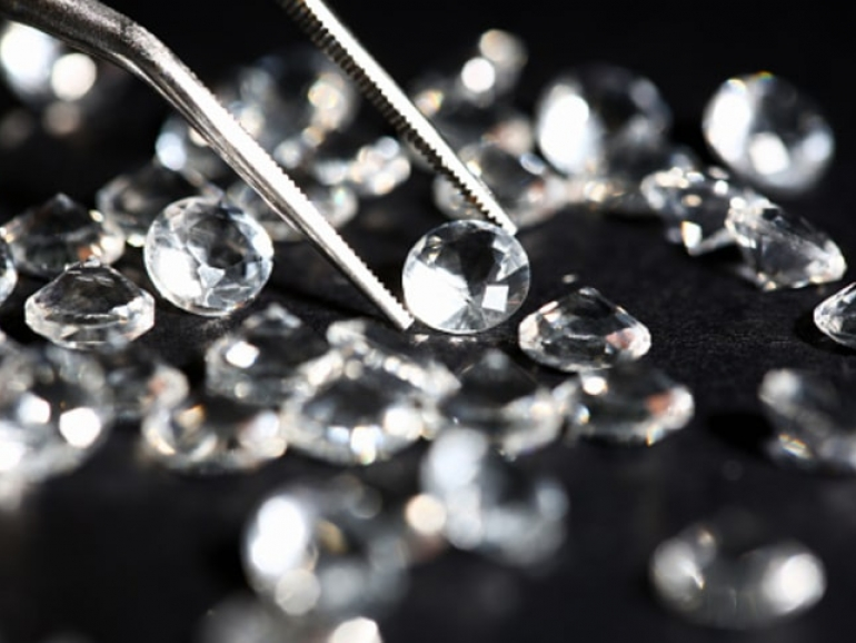 Scattering of white star diamonds on black background table jeweler concept
