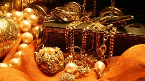Jewelry laying over a wooden, indian jewelry box on orange chiffon.