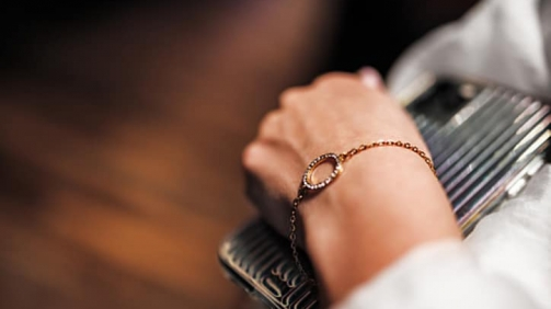 gold bracelet in the form of a ring with diamonds on a chain,girl's hand,sleeve of a white shirt,dark background.
